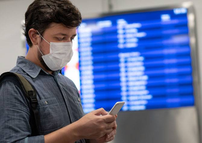 A man at an airport wearing a mask
