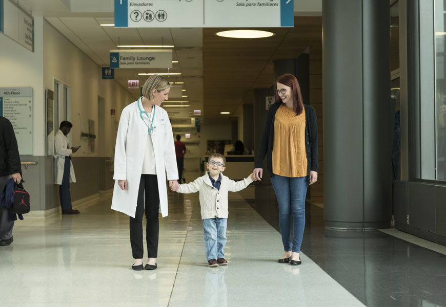 Young boy smiling walks holding hands with mother and doctor