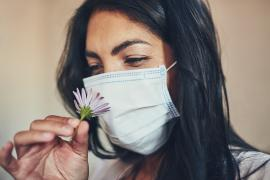 woman in mask smelling flower