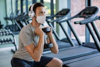 Man wearing mask while lifting weights