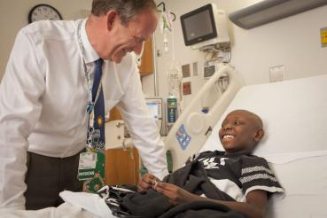 Doctor at bedside talking with smiling child.