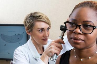 An audiologist conducts an ear exam