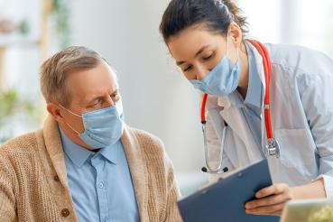 Doctor and patient wearing masks looking at paperwork