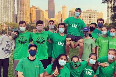 A softball team wearing Rush shorts and masks poses together in a park