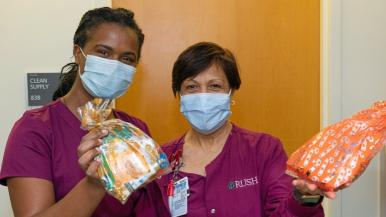 Two health care workers in scrubs and masks hold up colorful care packages